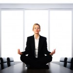 Business woman meditating on desk