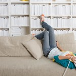 Woman on phone lying on couch w books